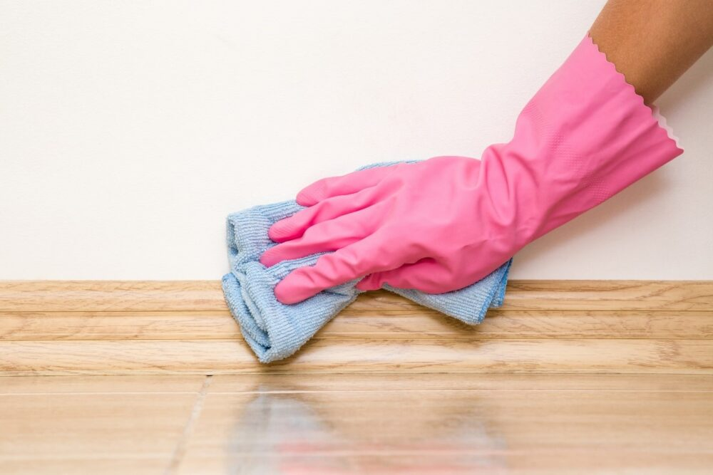 Hand in a pink rubber glove cleaning a baseboard